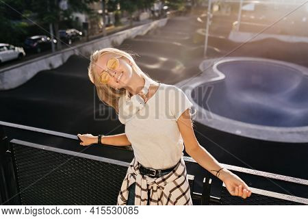 Excited Fair-haired Girl Posing With Eyes Closed In Skate Park. Outdoor Photo Of Glad Young Lady Rel
