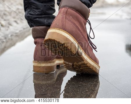 A Man Walks Through A Puddle In Terracotta Leather Shoes. Close-up, Reflection In A Puddle, Littered