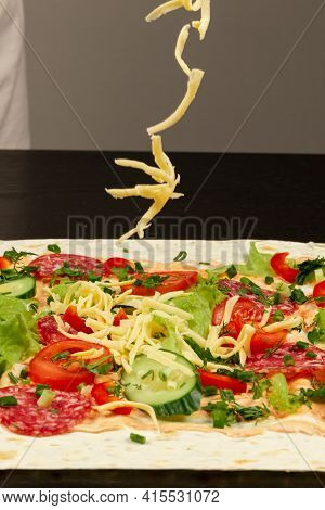 Female Hand Sprinkles Fresh Grated Cheese On Unwrapped Shawarma With Chopped Vegetables And Salami S