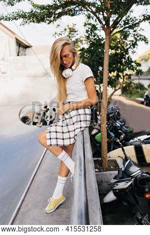 Fashionable Skater Girl With Long Hair Standing On The Street. Attractive Slim Woman In Sunglasses H