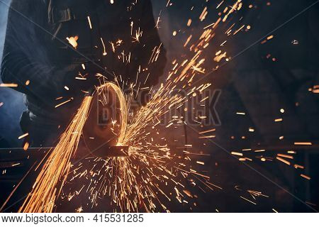 Close Up Of Worker Cutting Metal Pipe With Large Yellow Sparks. Concept Of Working With Angle Grinde