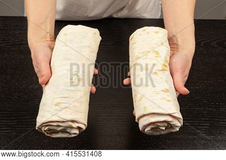 Female Hands Hold Two Freshly Prepared Shawarma On The Background Of A Black Wooden Table Close-up