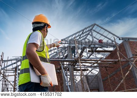 Engineer Technician Looking Up Roof Structure And Analyzing An Unfinished Construction Project