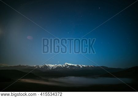 Atmospheric Night Landscape With Dense Fog And Great Snowy Mountain Ridge Under Starry Sky. Alpine S