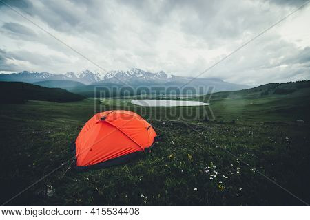 Atmospheric Alpine Landscape With Orange Tent On Background Of Lake And Big Snowy Mountains In Overc