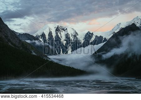 Scenic Landscape With Great Snowy Mountains On Sunset And Dense Low Clouds In Mountain Valley With F