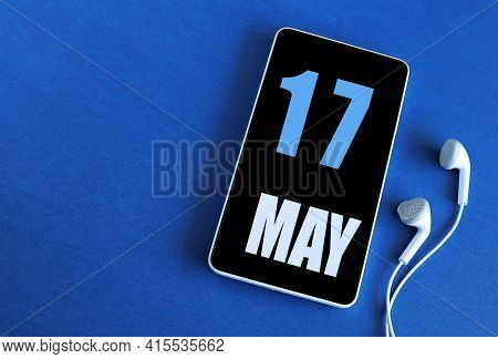 May 17. 17 St Day Of The Month, Calendar Date. Smartphone And White Headphones On A Blue Background.