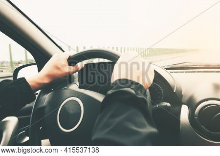 Close-up On Male Hands On The Steering Wheel Of A Car On A Blurred Background Of The Highway. Image