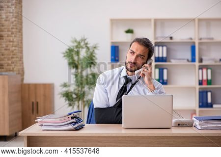 Young arm injured male employee working in the office
