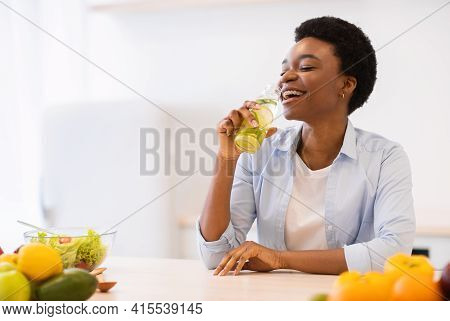 Black Woman Drinking Infused Water For Healthy Hydration In Kitchen