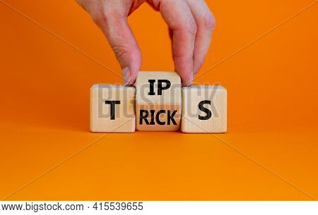 Tips And Tricks Symbol. Businessman Turn The Wooden Cube And Changes The Word 'tips' On 'tricks'. Be