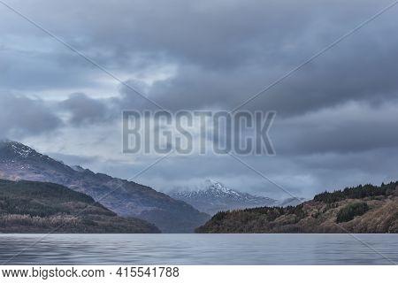 Beautiful Landscape Image Across Loch Lomond Looking Towards Snow Capped Ben Lui Mountain Peak In Sc