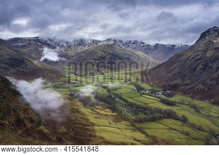 Epic Flying Drone Landscape Image Of Langdale Pikes And Valley In Winter With Low Level Clouds And M