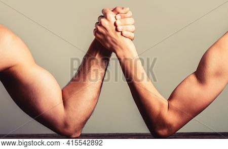 Arm Wrestling Thin Hand And A Big Strong Arm In Studio. Two Mans Hands Clasped Arm Wrestling, Strong
