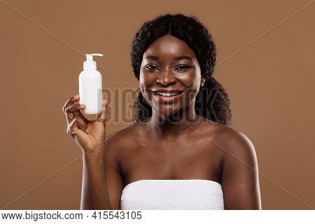 Body Skin Moisturising. Attractive Black Female In Towel Holding Bottle With Lotion