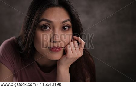Close-up Of A Young Woman With A Satisfied Facial Expression - Studio Photography