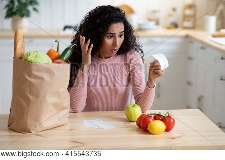 Portrait Of Shocked Young Housewife Checking Grocery Bills In Kitchen After Shopping