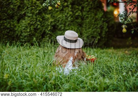 Young Girl With Long Hair In Summer Hat And White Overalls Sitting By Her Back In The Grass With A H