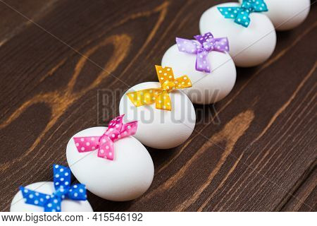 Line Of Easter Eggs With Colorful Bows Are On The Wooden Background