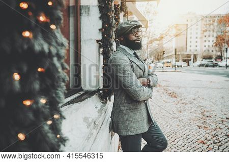 Portrait Of A Dapper Bearded Handsome African Guy In A Woolen Cap, Stylish Eyeglasses, And Elegant C