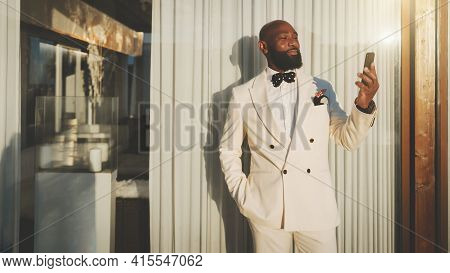 An Outdoor Portrait Of A Dapper Cheerful Mature Bald Bearded Black Guy In An Elegant White Suit, Hav