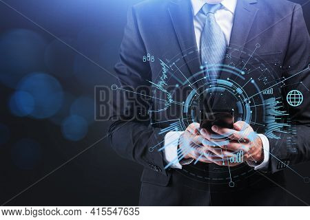 Businessman Wearing Formal Suit Holds The Smart Phone. Mobile Is Surrounded By Circle Hologram With
