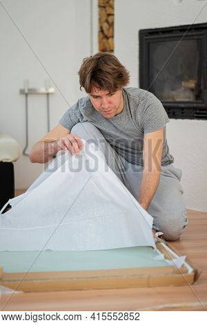 Young Man Opening A Carton Packaging To Unwrap A Furniture In A Home Diy Project.