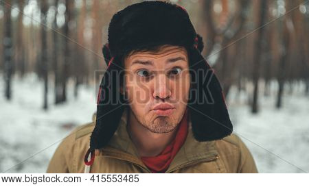 Man Grimaces In Forest In Winter Season. Portrait Of Crazy Male Wearing Earflap Hat And Grimacing Fa
