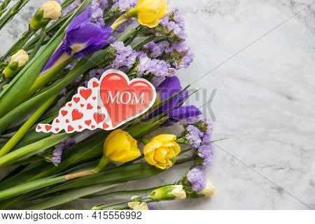 Romantic Background With Bouquet Of Yellow Narcissus Flowers And Purple Irises, Statice Flowers.happ