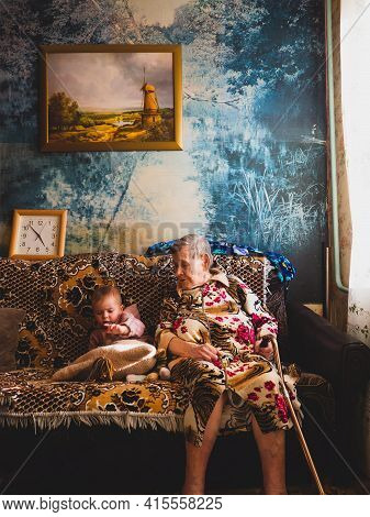 Moscow 02.04.2021. A Beautiful Little Girl Is Sitting On The Sofa With Her Very Old Grandmother, The
