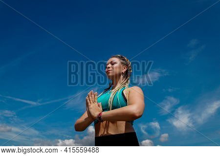 Caucasian Woman With Dreadlocks In Meditation Posture With The Sky In The Background
