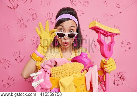 Photo Of Stupefied Housewife Keeps Hand On Sunglasses Holds Mop Busy Doing Laundry Poses Indoor Surr
