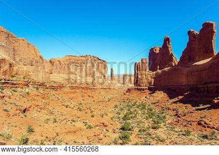 USA. Picturesque red-brown sandstone cliffs form a unique landscape. The unique beauty of Arches Park. Grandiose rock compositions created by nature. Park Avenue viewpoint