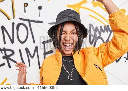 Urban Style Lifestyle Youth And Emotions Concept. Positive Carefree Hipster Girl Has Dreadlocks Rais