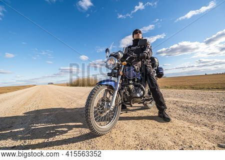 Man In A Black Uniform On Bike Against The Backdrop Of Panorama Of Field And Blue Sky. Motorcycle Tr
