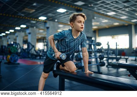 Youngster doing exercise with dumbbell on bench