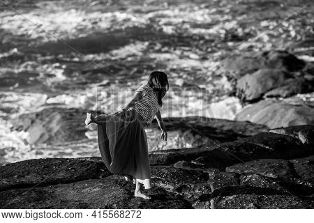 Dance woman is engaged in choreography on the ocean coast. Black and white photo.
