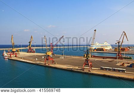 Harbor With Industrial Loading Dock For Ships In Heraklion, Crete, Greece With A Cruise Ship Docked