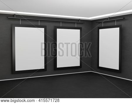 Three Images Hang On A Dark Gray Concrete Wall In The Corner Of The Room. Poster Template With Black