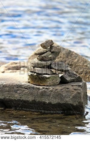 A Cairn Stack On A Large Flat Rock Near Water