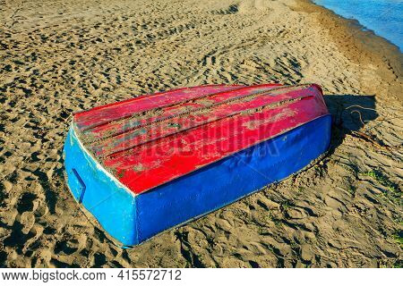 Upside Down Boat On The Beach . Boat Colored In Red And Blue