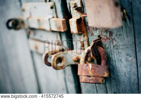 A Rusty Old Lock On A Blue Old Wooden Door. A Gate Closed On The Lock.