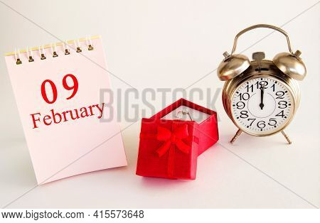 Calendar Date On Light Background With Red Gift Box With Ring And Alarm Clock With Copy Space. Febru