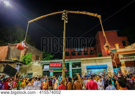 Howrah, West Bengal,india - 15th April 2019: Hindu Devotee Playing Drum While Hanging From Pole In A