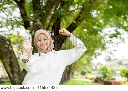 Muslim Woman With Head Scarf Drinking A Bottle Of Water During Exercising Outdoor