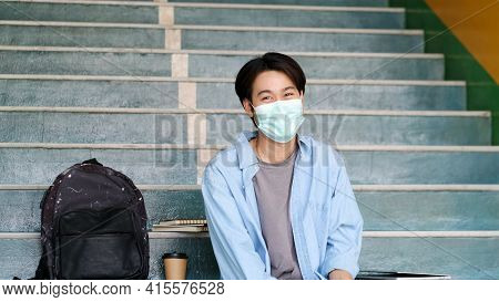 Young Asian Campus Student Man Wearing Protection Mask Smiling And Looking At Camerawhile Sitting In