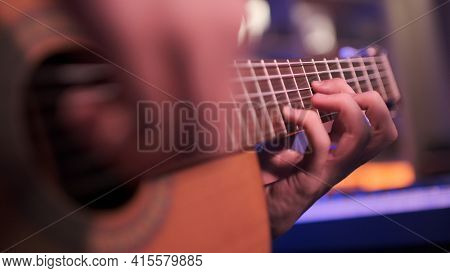 Close-up of a man's hands playing the guitar. The musician plays an acoustic guitar, closeup shot. Male fingers  plays on guitar. human hands plays on a guitar neck, soft focus