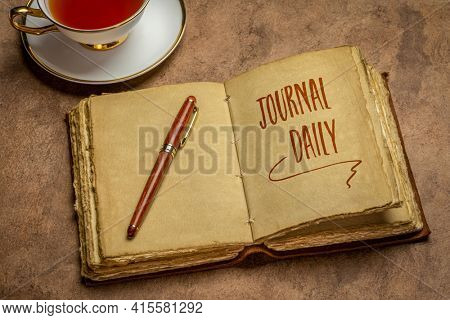 journal daily inspirational advice - handwriting in an antique leather-bound journal with decked edge handmade paper pages with a stylish pen and cup of tea against handmade paper, journaling concept