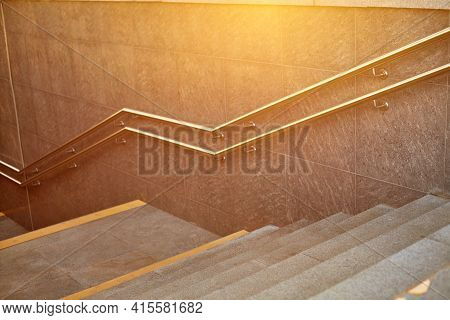 Modern Underground Passage. Steps And Handrails In The Foreground. The Walls And Floor Of The Passag