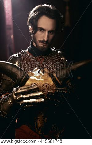 Noble knight in armor holds in his hands skull of a horned animal in a medieval castle. Historical shoot. Middle ages.